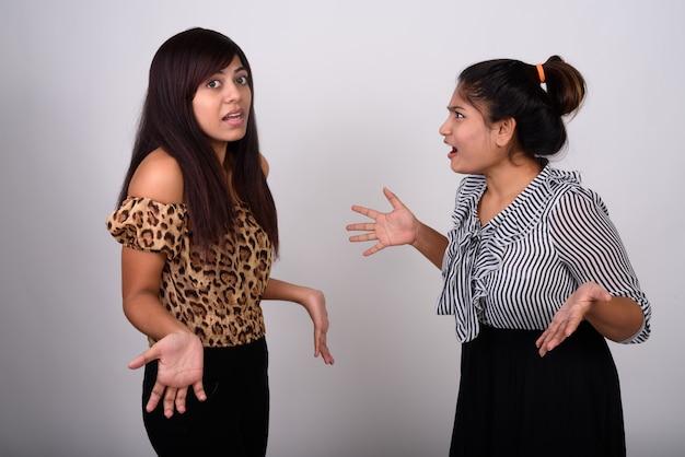 Giovane ragazza adolescente guardando confuso giovane donna