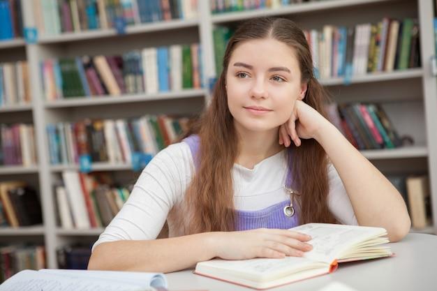 Giovane ragazza adolescente che studia in biblioteca