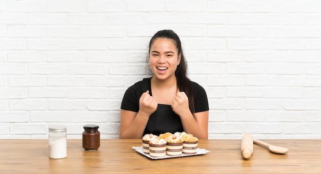Ragazza asiatica del giovane adolescente con i lotti della torta del muffin che celebra una vittoria
