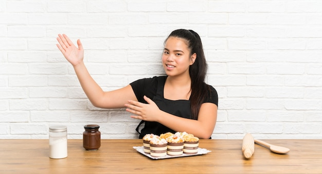 Ragazza asiatica del giovane adolescente con un sacco di torta del muffin che estende le mani al lato per l'invito a venire