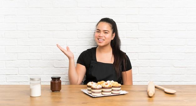 Ragazza asiatica del giovane adolescente con i lotti del muffin agglutinano il copyspace immaginario sulla palma
