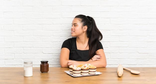 Ragazza asiatica del giovane adolescente con i lotti della torta del muffin che osserva al lato