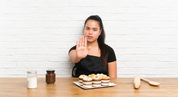 Ragazza asiatica del giovane adolescente con i lotti della torta del muffin che fa gesto di arresto con la sua mano
