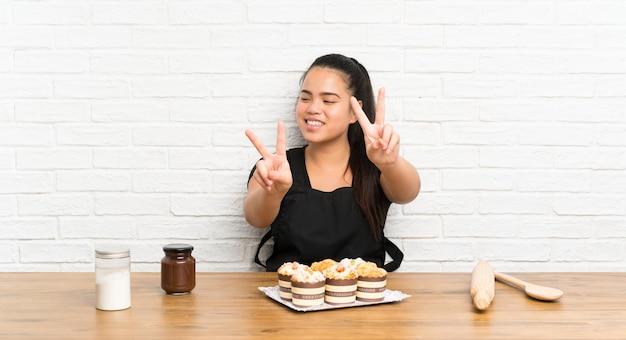 Ragazza asiatica del giovane adolescente con i lotti della torta del muffin che sorride e che mostra il segno di vittoria