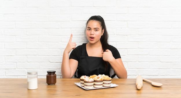 Ragazza asiatica del giovane adolescente con i lotti della torta del muffin con espressione facciale di sorpresa