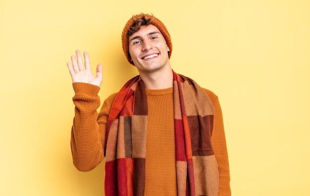 Giovane ragazzo adolescente che sorride allegramente e allegramente, agitando la mano, accogliendoti e salutandoti, o salutandoti