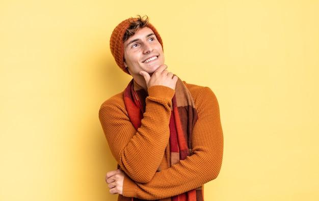 Ragazzo giovane adolescente che sorride felicemente e sogna ad occhi aperti o dubita, guardando di lato