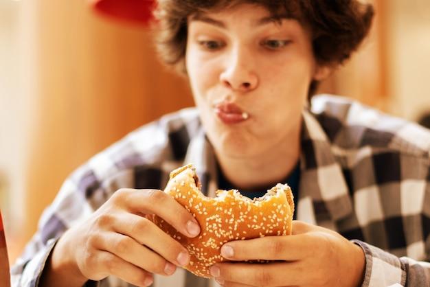 Giovane adolescente che mangia hamburger eating