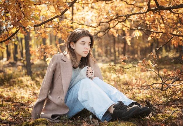 Ragazza giovane adolescente nella foresta autunnale. colori autunnali. stile di vita. atmosfera autunnale. foresta