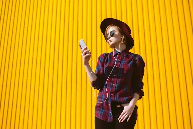Giovane ragazza dell'adolescente con la bevanda e telefono in sue mani che posano sopra il fondo giallo variopinto vuoto. ragazza hipster