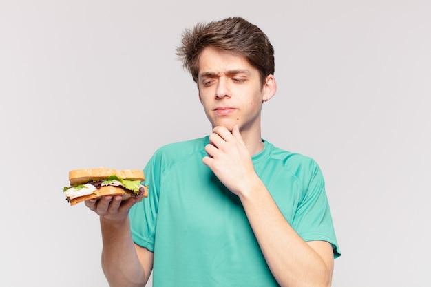 Giovane uomo dell'adolescente che dubita o dell'espressione incerta e che tiene un panino