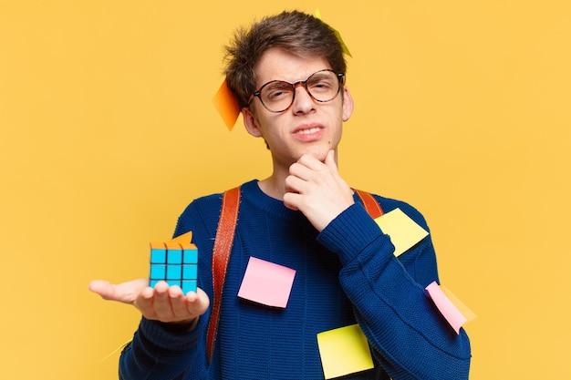 Giovane uomo dell'adolescente che dubita o espressione incerta. concetto di studente universitario