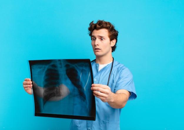 Espressione spaventata dell'uomo del giovane adolescente. concetto di infermiera