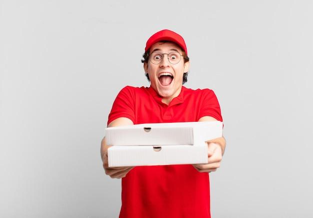 La giovane pizza dell'adolescente consegna l'espressione sorpresa dell'uomo