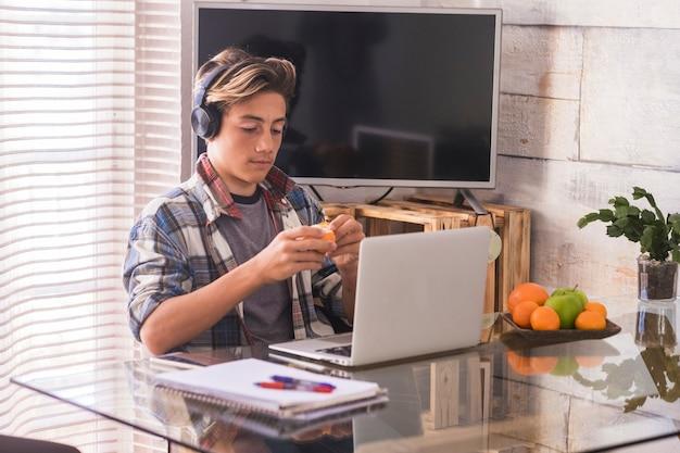 Giovane adolescente che lavora a casa in silenzio con le cuffie - ascolta musica mentre fai i compiti e mangia un'arancia - sfondo domestico e molta frutta sul tavolo