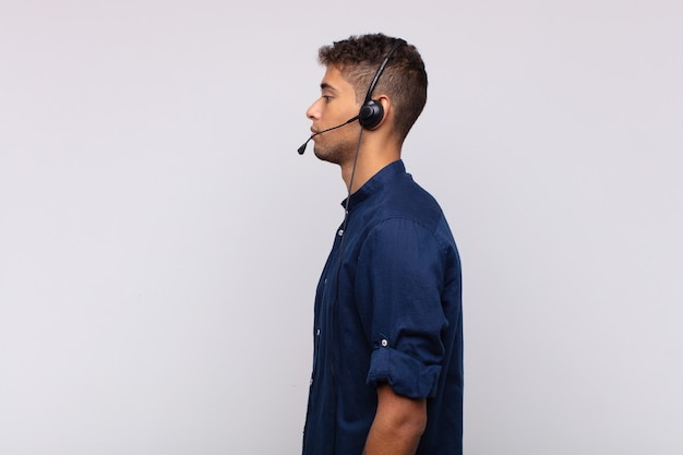 Giovane uomo telemarketer sulla vista di profilo che cerca di copiare lo spazio avanti, pensare, immaginare o fantasticare