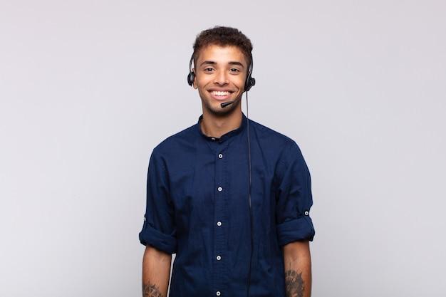 Giovane uomo di telemarketing che sorride felicemente con una mano sull'anca e un atteggiamento fiducioso, positivo, orgoglioso e amichevole