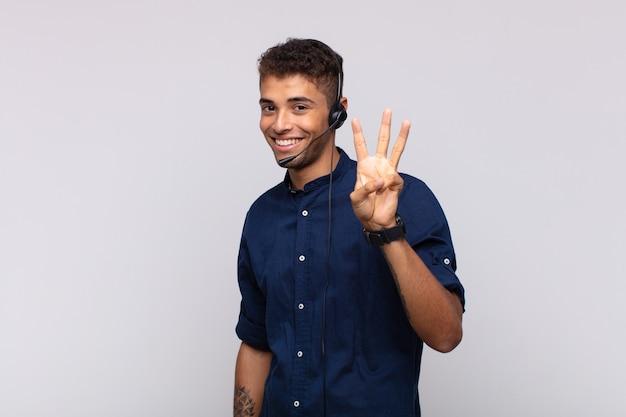 Giovane uomo telemarketer sorridente e guardando amichevole, mostrando il numero tre o terzo con la mano in avanti, conto alla rovescia