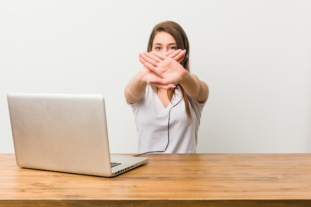 Giovane donna telemarketer che fa un gesto di rifiuto