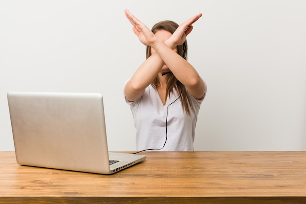Giovane donna telemarketer mantenendo due braccia incrociate, concetto di rifiuto.