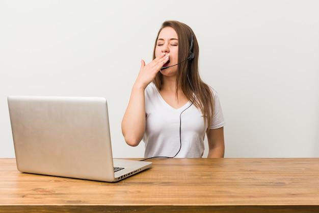 Giovane donna telemarketer che sbadiglia mostrando un gesto stanco che copre la bocca con la mano.