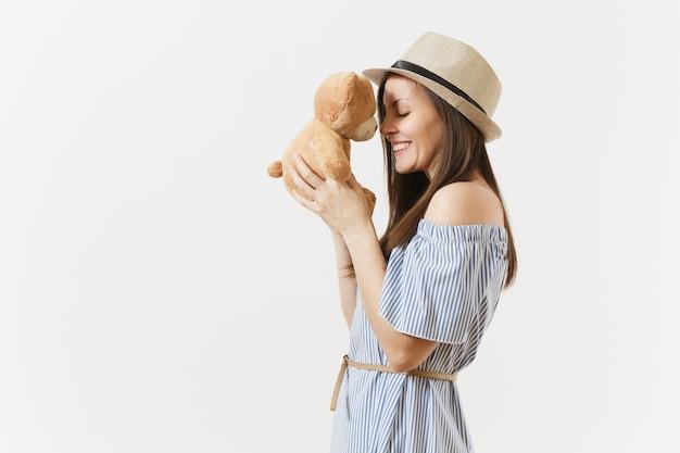 Giovane donna affascinante elegante tenera vestita vestito blu, cappello carino abbraccio simpatico orsacchiotto in posa isolato su priorità bassa bianca. persone, emozioni sincere, concetto di stile di vita. zona pubblicità. copia spazio.