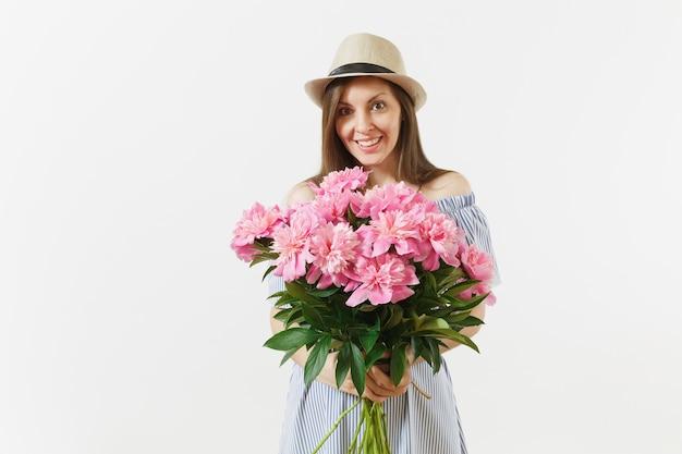 Giovane donna tenera in abito blu, cappello con bouquet di bellissimi fiori di peonie rosa isolati su sfondo bianco. san valentino, concetto di vacanza per la giornata internazionale della donna. zona pubblicità.