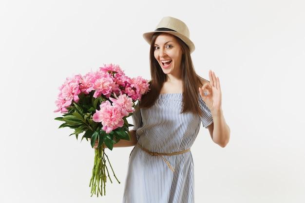 Giovane donna tenera in abito blu, cappello con bouquet di bellissimi fiori di peonie rosa, che mostra gesto ok isolato su sfondo bianco. san valentino, concetto di vacanza per la giornata internazionale della donna