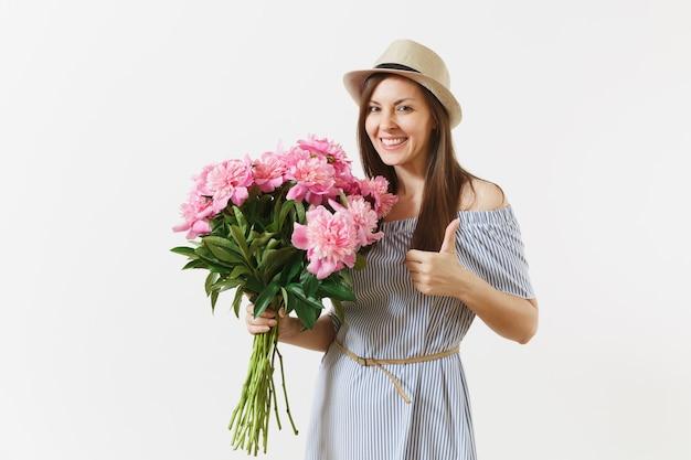 Giovane donna tenera in abito blu, cappello con bouquet di bellissimi fiori di peonie rosa, che mostra i pollici in su isolati su sfondo bianco. san valentino, concetto di vacanza per la giornata internazionale della donna.
