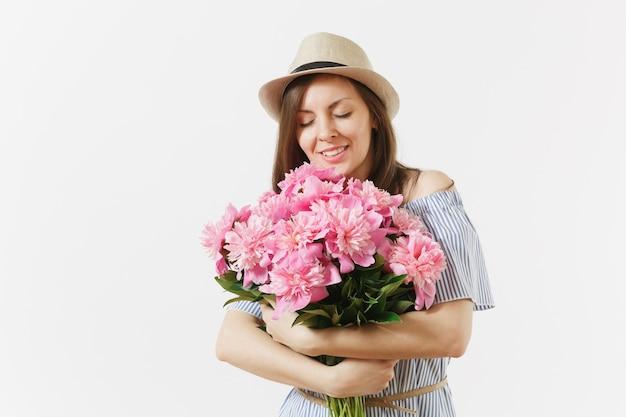 Giovane donna tenera in abito blu, cappello che tiene, sniffing bouquet di fiori di peonie rosa isolati su sfondo bianco. san valentino, concetto di vacanza per la giornata internazionale della donna. zona pubblicità.