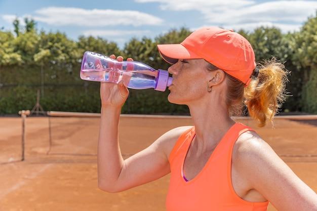 Giovane tennista beve l'acqua sul campo