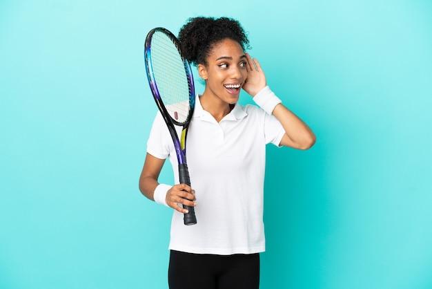 Giovane donna del giocatore di tennis isolata su fondo blu che ascolta qualcosa mettendo la mano sull'orecchio