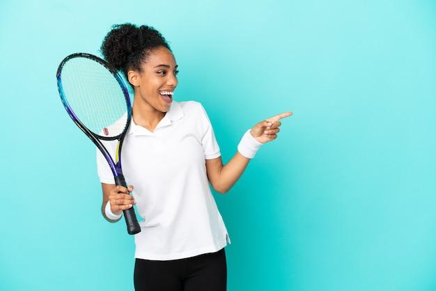 Donna giovane giocatore di tennis isolata su sfondo blu che punta il dito sul lato e presenta un prodotto