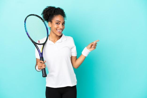 Giovane donna del giocatore di tennis isolata su fondo blu che indica dito al lato