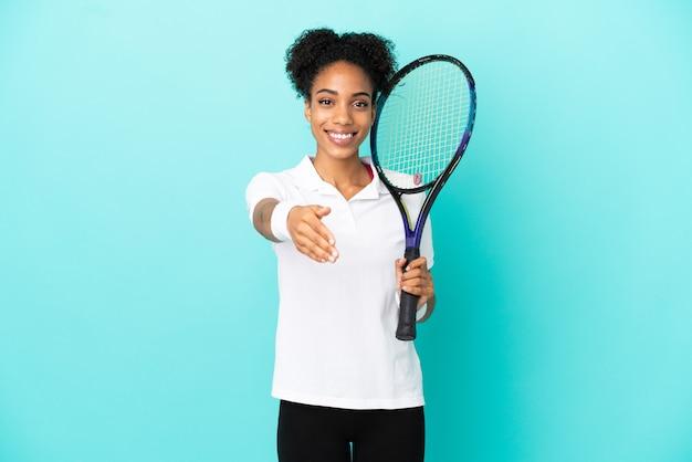 Giovane donna del giocatore di tennis isolata su fondo blu che stringe la mano per la chiusura di un buon affare