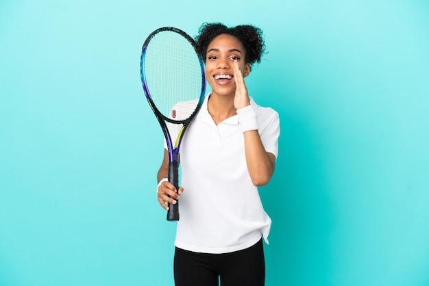 Giovane donna del giocatore di tennis isolata su fondo blu che grida con la bocca spalancata