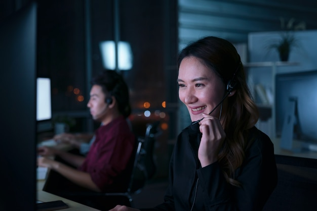 I giovani operatori asiatici tailandesi di assistenza clienti lavorano il turno di notte nel call center