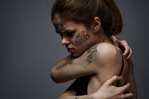 Giovane donna magra con insulti sulle iscrizioni del corpo, parolacce, stato depresso, solitudine
