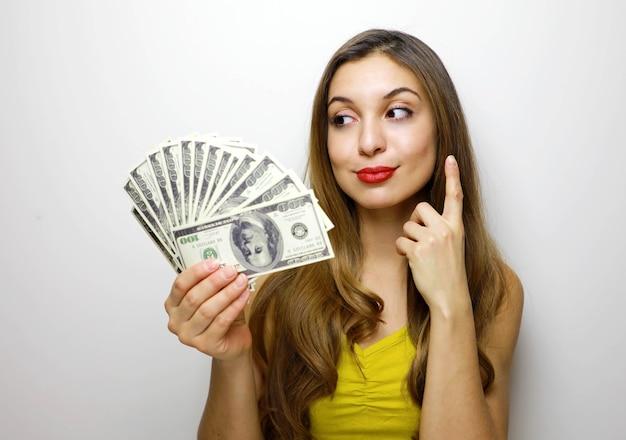 Giovane donna graziosa di pensiero in vestito giallo con il mazzo di banconote dei soldi