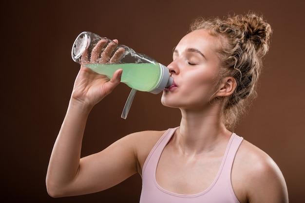 Giovane donna attiva assetata con capelli ricci biondi con bevanda rinfrescante dalla bottiglia di plastica dopo l'allenamento in palestra o centro lesiure