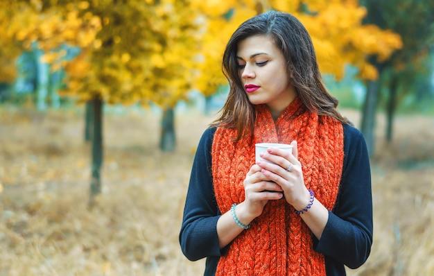 Giovane ragazza premurosa con una tazza di caffè nel parco d'autunno all'aria aperta. pioggia calda e leggera.
