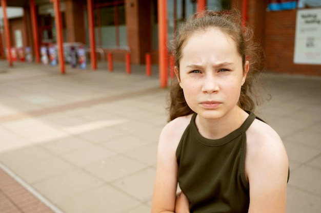 Giovane ragazza premurosa di età adolescente che guarda l'obbiettivo, ritratto all'aperto di una ragazza triste