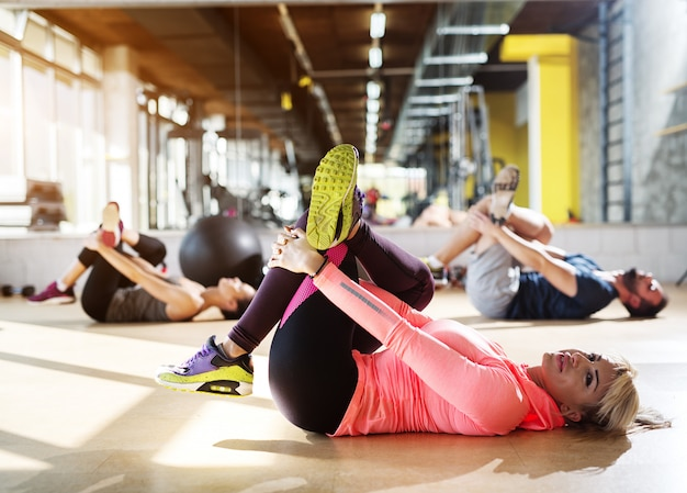 Giovani atleti stanchi in una palestra che allungano i muscoli delle gambe dopo la lezione di pilates.
