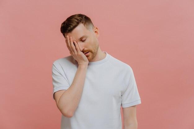 Giovane uomo barbuto stanco in maglietta bianca con gli occhi chiusi sentendosi assonnato, facendo il gesto del palmo mentre posa su sfondo rosa pastello, mettendosi la mano sul viso e mostrando delusione