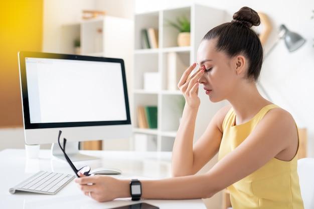Giovane imprenditrice stanca in abito giallo seduto da scrivania davanti al monitor del computer nel bel mezzo della giornata lavorativa