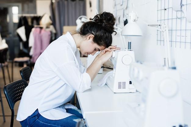 Giovane sarta stanca o malata seduta alla scrivania e tenendo la testa sulla macchina da cucire elettrica in officina