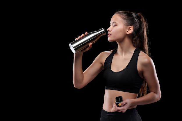 Giovane sportiva stanca in acqua potabile activewear dalla bottiglia di metallo dopo l'allenamento in isolamento