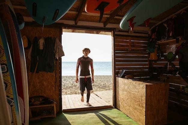 Ragazzo giovane surfista stanco andando alla capanna di surf in spiaggia