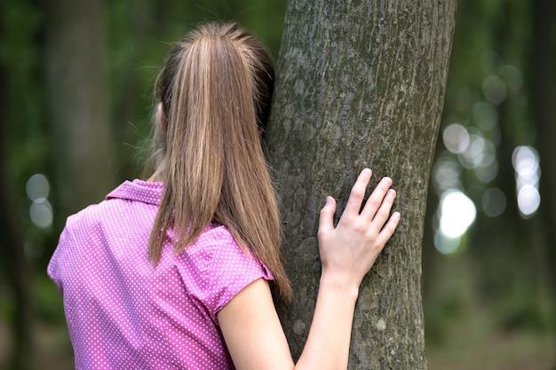 Giovane donna stanca che riposa appoggiata al tronco d'albero nella foresta estiva.