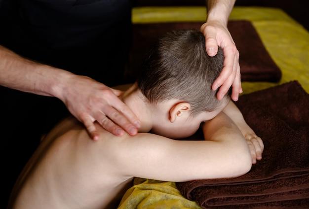 Il giovane bambino si rilassa da un massaggio terapeutico. le mani di un massaggiatore